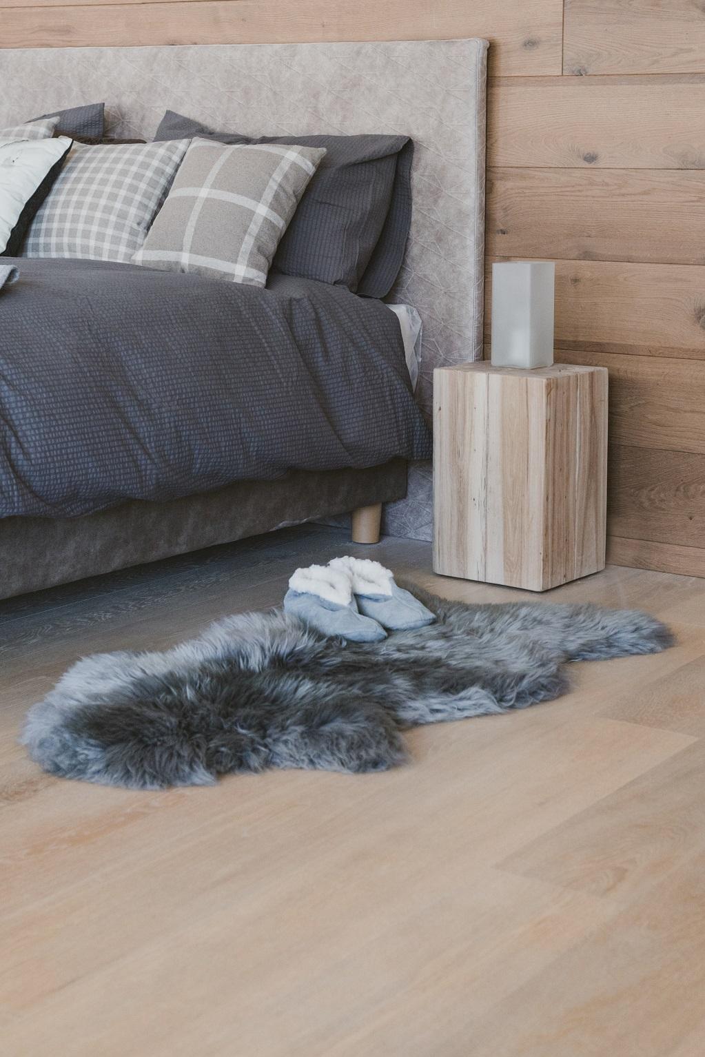 toni del grigio sul letto stile minimalista e sul tappeto di vera pelle di montone